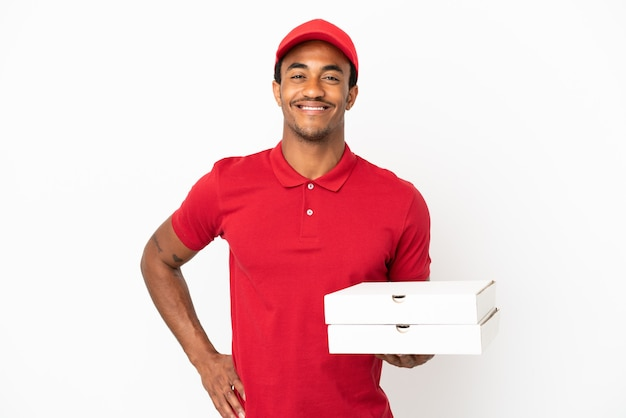 Afroamerikanischer pizzabote, der pizzakartons über isolierter weißer wand aufhebt, die mit armen an der hüfte posiert und lächelt