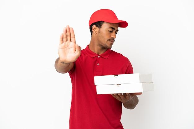 Afroamerikanischer pizzabote, der pizzakartons über isolierter weißer wand aufhebt, die stopp-geste macht und enttäuscht