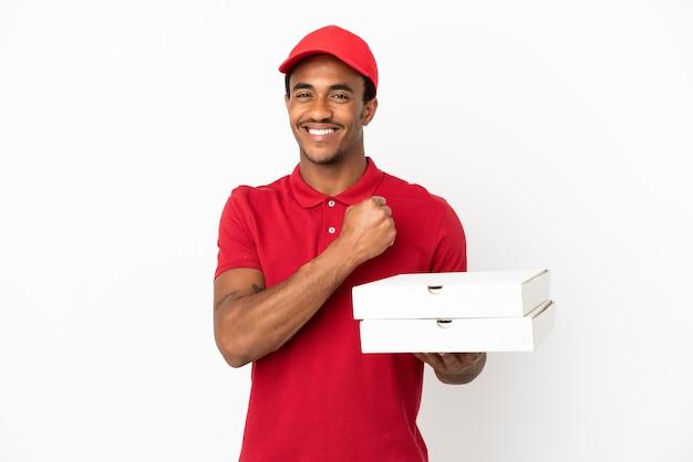 Afroamerikanischer pizzabote, der pizzakartons über isolierter weißer wand aufhebt und einen sieg feiert