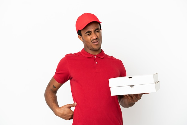 Afroamerikanischer pizzabote, der pizzakartons über isolierter weißer wand aufhebt und unter rückenschmerzen leidet, weil er sich bemüht hat?