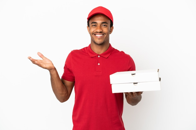 Afroamerikanischer pizzabote, der pizzakartons über isolierter weißer wand aufhebt und zweifel hat, während er die hände hebt