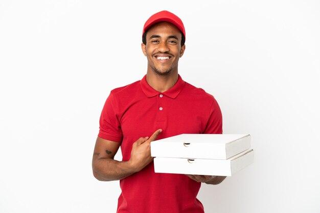 Afroamerikanischer pizzabote, der pizzakartons über isolierter weißer wand mit überraschendem gesichtsausdruck aufhebt