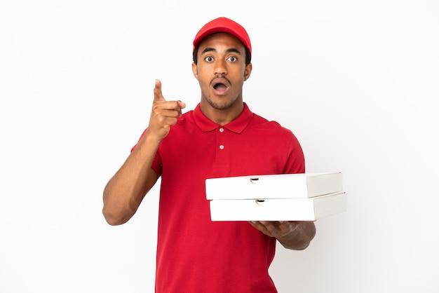 Afroamerikanischer pizzalieferant, der pizzakartons über isolierter weißer wand aufhebt, um die lösung zu realisieren, während er einen finger hochhebt