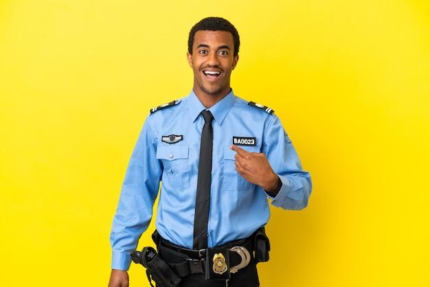 Afroamerikanischer polizist über isoliertem gelbem hintergrund mit überraschtem gesichtsausdruck