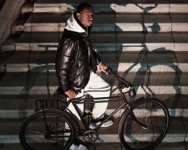 Afroamerikanischer radfahrer der seitenansicht, der die treppe klettert