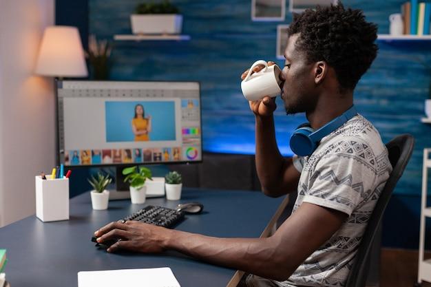 Afroamerikanischer redakteur, der kaffee trinkt, während er fotoretusche macht