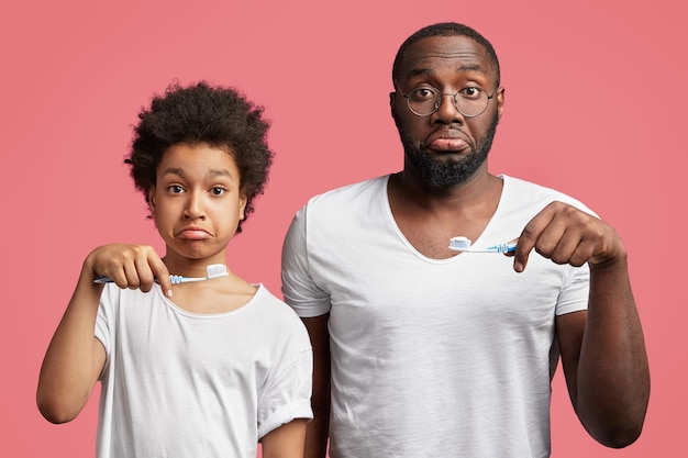 Afroamerikanischer sohn und vater halten zahnbürsten