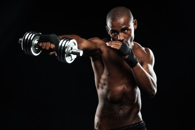 Afroamerikanischer sportler, der sich wie ein kampf mit hanteln ausgibt