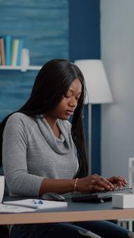 Afroamerikanischer student, der am schreibtisch sitzt, beginnt mit der eingabe von online-hausaufgaben am computer