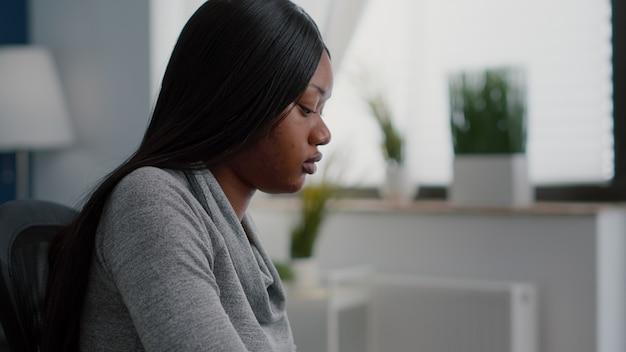 Afroamerikanischer student, der am schreibtisch sitzt und kommunikationsprojekt auf dem computer tippt