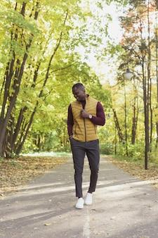 Afroamerikanischer student, der in der herbstsaison im park spazieren geht