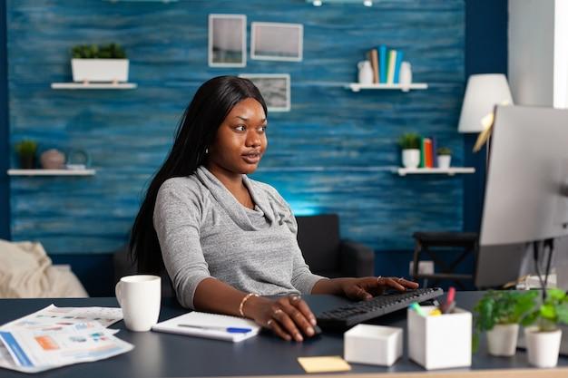 Afroamerikanischer student, der kommunikationsinformationen auf dem computer durchsucht