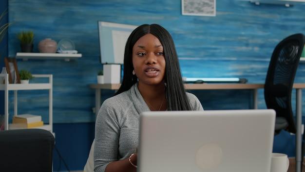 Afroamerikanischer student, der von zu hause aus arbeitet und mit schulprofessor diskutiert