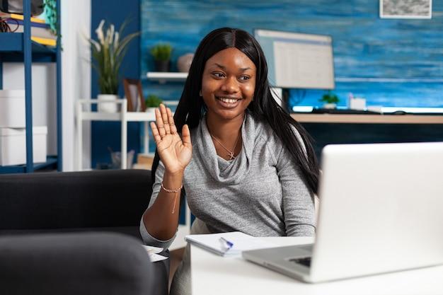 Afroamerikanischer student winkt akademischen kollegen während der online-videokonferenz-konferenz