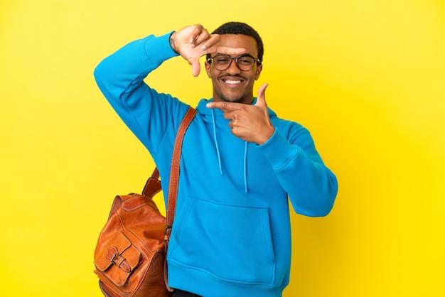 Afroamerikanischer studentenmann über isoliertem gelbem hintergrund, der das gesicht fokussiert. rahmensymbol