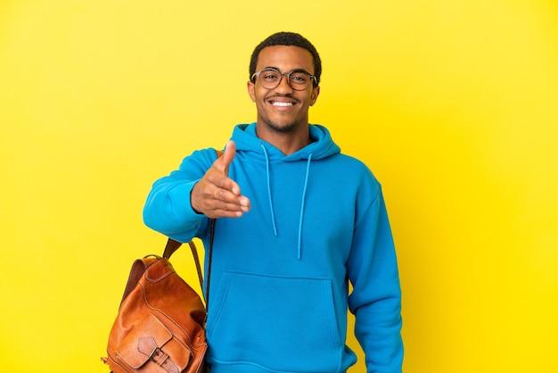 Afroamerikanischer studentenmann über isoliertem gelbem hintergrund, der hände schüttelt, um ein gutes geschäft abzuschließen