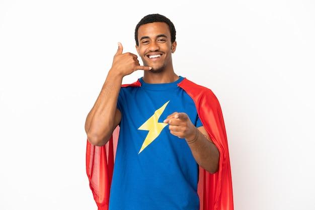 Afroamerikanischer superheld-mann über isoliertem weißem hintergrund, der telefongeste macht und nach vorne zeigt