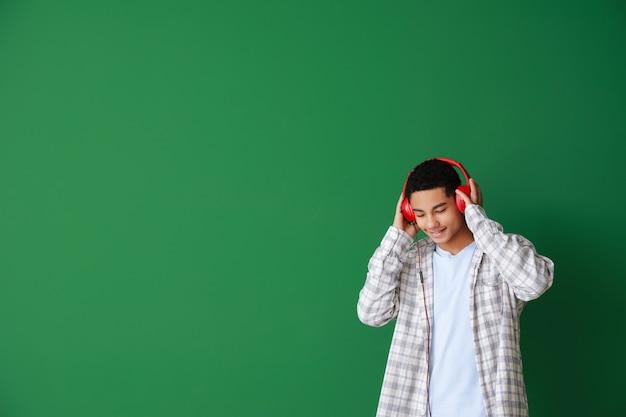 Afroamerikanischer teenager, der musik auf grün hört