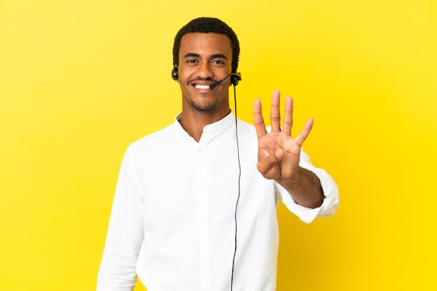 Afroamerikanischer telemarketer-mann, der mit einem headset über isoliertem gelbem hintergrund arbeitet, glücklich und zählt vier mit den fingern count