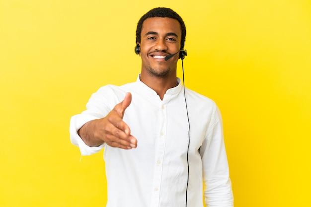 Afroamerikanischer telemarketer-mann, der mit einem headset über isoliertem gelbem hintergrund arbeitet und sich die hände schüttelt, um ein gutes geschäft abzuschließen