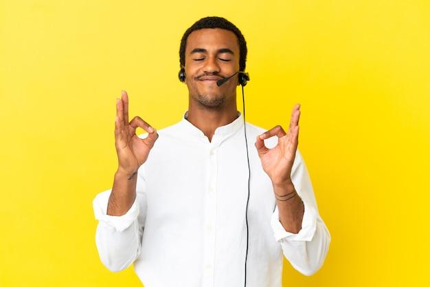 Afroamerikanischer telemarketer-mann, der mit einem headset über isoliertem gelbem hintergrund in zen-pose arbeitet