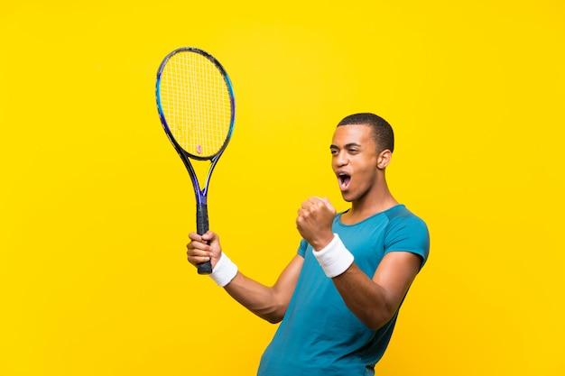 Afroamerikanischer tennisspielermann auf gelb