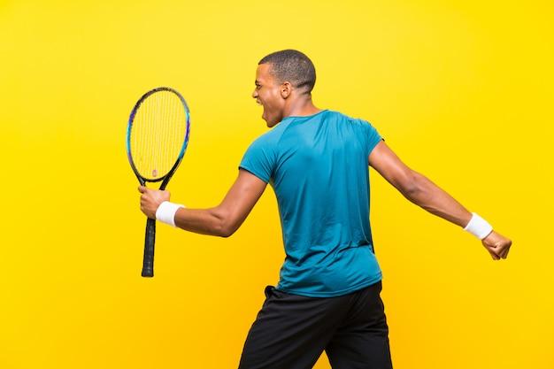 Afroamerikanischer tennisspielermann über getrenntem gelb
