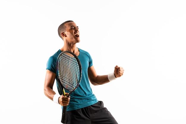 Afroamerikanischer tennisspielermann über getrenntem weißem hintergrund