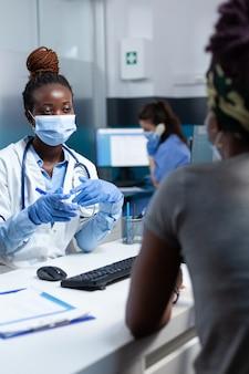 Afroamerikanischer therapeut arzt bespricht mit kranken patienten