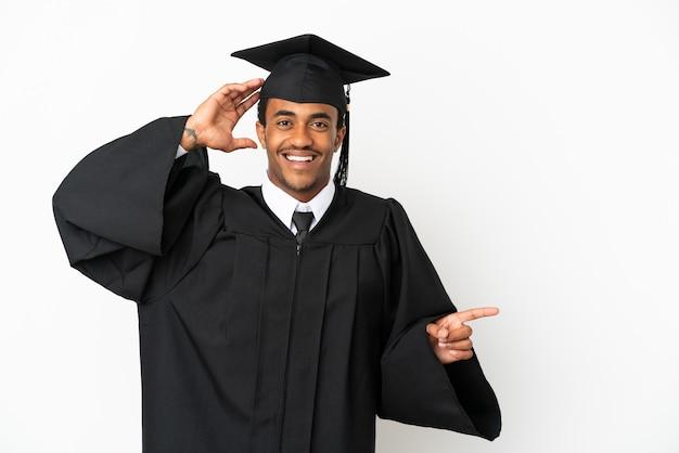 Afroamerikanischer universitätsabsolvent über isoliertem weißem hintergrund überrascht und zeigt mit dem finger zur seite