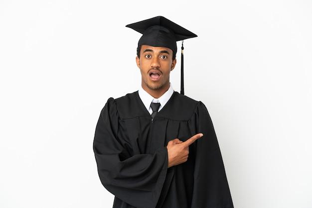 Afroamerikanischer universitätsabsolvent über isoliertem weißem hintergrund überrascht und zeigt seite