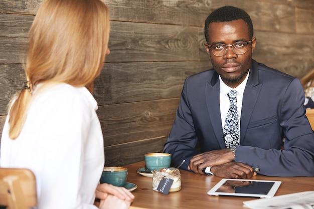 Afroamerikanischer unternehmer, der formellen anzug und brille trägt