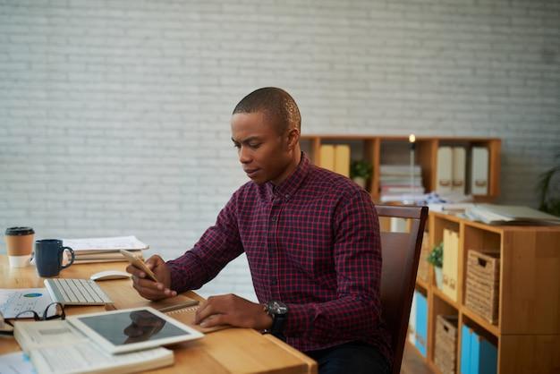Afroamerikanischer unternehmer mit smartphone