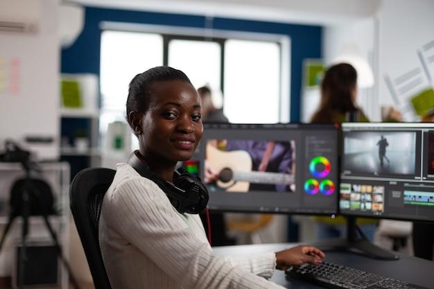 Afroamerikanischer video-editor-künstler, der lächelnd in die kamera schaut und das kreativitätsvideoprojekt bearbeitet