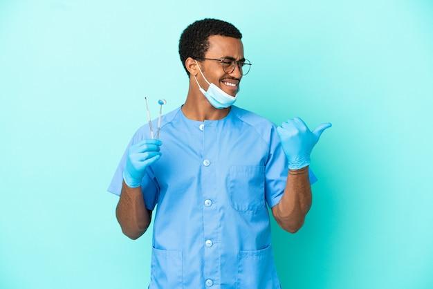 Afroamerikanischer zahnarzt, der werkzeuge über isoliertem blauem hintergrund hält, der auf die seite zeigt, um ein produkt zu präsentieren