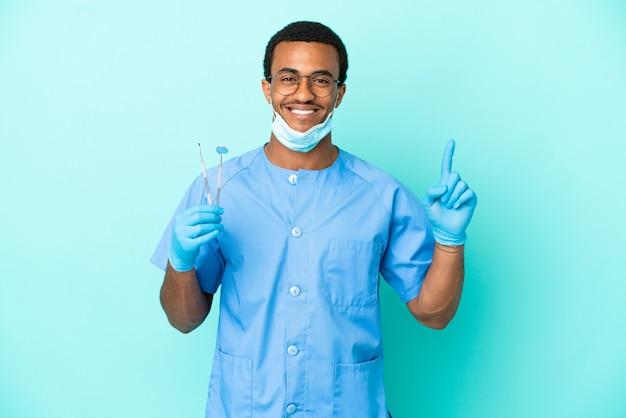 Afroamerikanischer zahnarzt, der werkzeuge über isoliertem blauem hintergrund hält, die auf eine großartige idee hinweisen