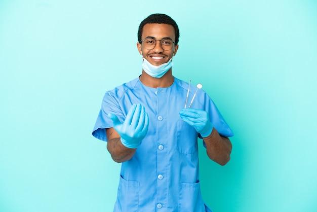 Afroamerikanischer zahnarzt, der werkzeuge über isoliertem blauem hintergrund hält, die einladen, mit der hand zu kommen. schön, dass du gekommen bist