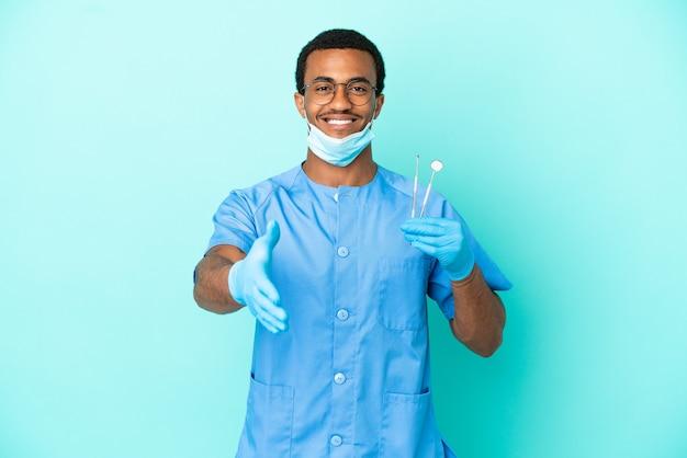 Afroamerikanischer zahnarzt, der werkzeuge über isoliertem blauem hintergrund hält, die hände schütteln, um ein gutes geschäft abzuschließen