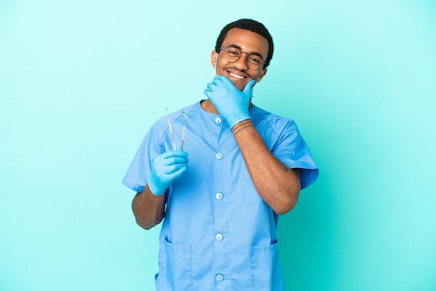 Afroamerikanischer zahnarzt, der werkzeuge über isoliertem blauem hintergrund hält, glücklich und lächelnd