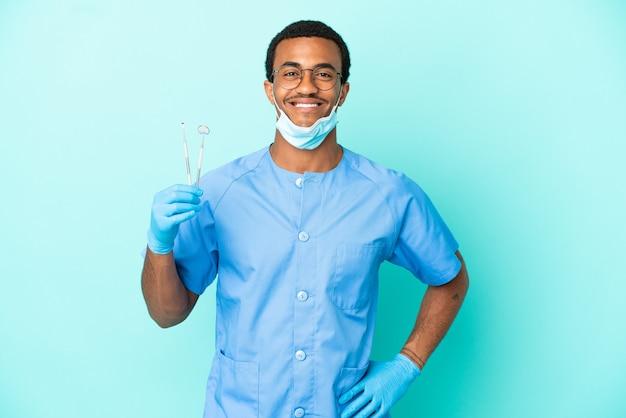 Afroamerikanischer zahnarzt, der werkzeuge über isoliertem blauem hintergrund hält und mit armen an der hüfte posiert und lächelt