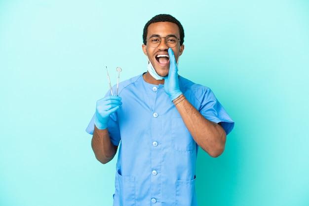 Afroamerikanischer zahnarzt, der werkzeuge über isoliertem blauem hintergrund hält und mit weit geöffnetem mund schreit