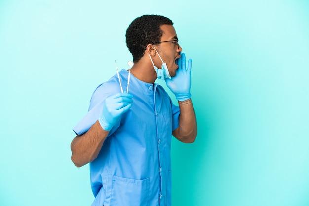 Afroamerikanischer zahnarzt, der werkzeuge über isoliertem blauem hintergrund hält und mit weit geöffnetem mund zur seite schreit