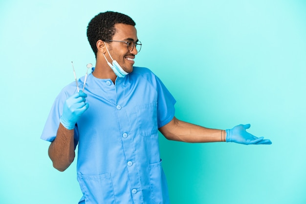 Afroamerikanischer zahnarzt, der werkzeuge über isoliertem blauem hintergrund mit überraschungsausdruck hält, während er zur seite schaut