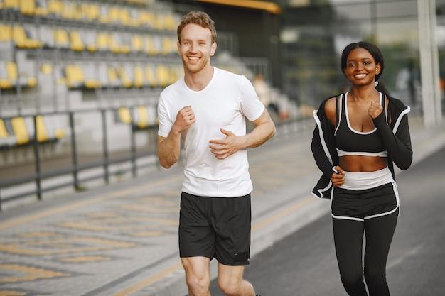 Afroamerikanisches fitness-model und kaukasischer mann, der im freien joggt