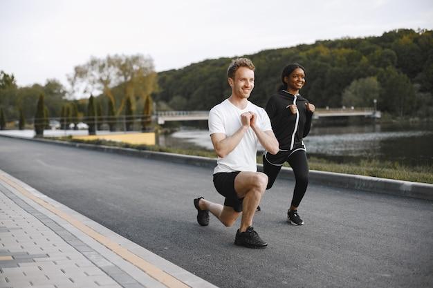 Afroamerikanisches fitnessmodell und kaukasischer mann trainieren im freien