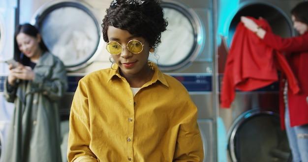 Afroamerikanisches junges hübsches und stilvolles mädchen in den gelben gläsern, die im wäscheservice-raum stehen und seiten des modejournals umblättern. frauenlesemagazin beim warten auf gewaschene kleidung.