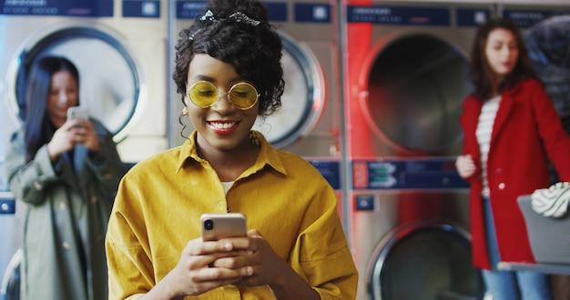 Afroamerikanisches junges hübsches und stilvolles mädchen in gelben gläsern, die im wäscheservice-raum stehen und auf smartphone tippen. frau sms am telefon während des wartens auf kleidung gewaschen werden.