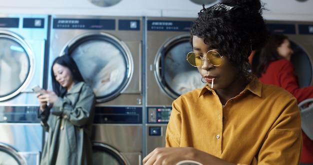 Afroamerikanisches junges schönes mädchen in gelben gläsern, die im wäscheservice-raum sitzen. frau mit lollypop-lesemagazin beim warten auf das waschen der kleidung im öffentlichen waschsalon.