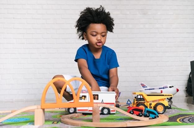 Afroamerikanisches kind, das zu hause mit autospielzeug spielt