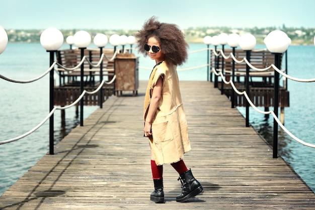 Afroamerikanisches kleines mädchen, das draußen stilvolle kleidung trägt. mode-kind-konzept